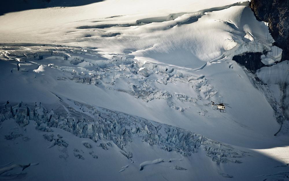 An MD 500 is dwarfed by an alpine glacier