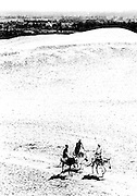 Cluster of three men riding donkeys while in conversation, along a road in the desert near Giza above Cairo.  High viewpoint from part way up the Great Pyramid.