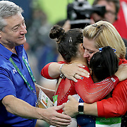 Gymnastics - Olympics: Day 6 Simone Biles #391 of the United States and Alexandra Raisman #395 of the United States and coach Aimee Boorman embrace as the final result comes through confirming gold and silver medal for the pair as coach Mihai Brestyan looks on during the Artistic Gymnastics Women's Individual All-Around Final at the Rio Olympic Arena on August 11, 2016 in Rio de Janeiro, Brazil. (Photo by Tim Clayton/Corbis via Getty Images)