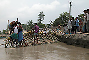 Village People try to build a bamboo and sand bank to prevent erosion at Salmara village, about 328 kilometers southwest of Gauhati, the capital city of Northeastern Indian state, Assam, Wednesday, June 30, 2004. .Floodwaters of the Asia'a one of the largest river, Brahmaputra and its 35 tributaries have affected more than one million in all of Indian subcontinent and disrupted communication in many parts of the India and Bangladesh, sources said. (AP Photo/ Shib Shankar Chatterjee)..