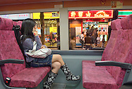 Downtown, Hong Kong, China. Young woman using mobile phone on bus outside cafes in Nathan Road, Tsim Sha Tsui district, Kowloon