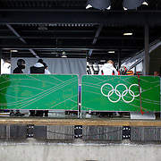 "Winter Olympics, Vancouver, 2010.Competitors prepare themselves behind the start area during the Bobsleigh, Four-Man heat two at The Whistler Sliding Centre, Whistler, during the Vancouver Winter Olympics. 24th February 2010. Photo Tim Clayton..'BOB'..Images from the Four-man Bobsleigh Competition. Winter Olympics, Vancouver 2010..History was made at the Whistler Sliding Centre when the USA four-man bobsleigh team, led by Steven Holcomb took the Gold. The first time since 1948, a gap of 62 years, since the USA have won an Olympic Bobsleigh gold and they did it with their sleigh named ""Night Train""...The four days of practice and competition show the tension, nervousness and preparation as the teams of hardened men cope with the challenge of traveling at average speeds of over 150 km an hour. Indeed, five teams had already pulled out of the event before the opening heats because of track complexity, speed and fear, and on the final day, another four teams did not start after six crashes in the first two heats...Teams warm up behind the start complex, warming muscles in the cold in preparation for the explosive start. Many teams prepare in silence, mentally preparing themselves as they wait at the top of the run, in the bobsleigh sheds and the loading areas for their turn. When it's time to slide each team performs it's own starting ritual, followed by the much practiced start out of the blocks for just over four seconds, the teams are then in the hands of the accomplished drivers as they hurtle down the track for just over fifty seconds...Spectators clamber for the best position on track to see the sleighs for a split second, many unsuccessfully try to capture the moments on camera, The rumble of the sleigh is heard then the crowds gasp as it hurtles past in a blur...The American foursome of  Steven Holcomb, Justin Olsen, Steve Mesler and Curtis Tomasevicz finished with a pooled four-heat time of 3min 24.46sec. The German team led by Andre Lange won the Silver Medal"