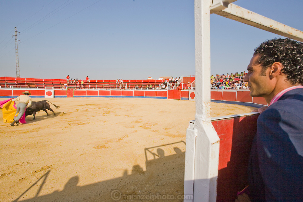 Professional Bullfighter Oscar Higares looks on as a fellow bullfighter performs at a bullfighting festival in Campos del Rio, near Murcia, Spain. (Oscar Higares is featured in the book What I Eat: Around the World in 80 Diets)
