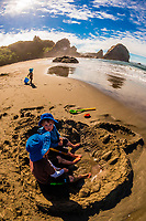Three brothers playing on the beach at Harris Beach State Park, Brookings, Oregon USA.