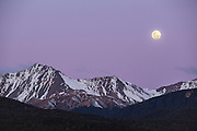 A full moon over a snowy mountain range along the Southern Alps, in Fiordland National Park, New Zealand.