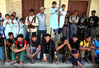 Maoist rebels of the People?s Liberation Army rest alongside some students at a school in a remote part of western Nepal on June 22, 2006. The ten-year old conflict in Nepal has claimed an estimated 13,000 lives. (Photo/Scott Dalton)
