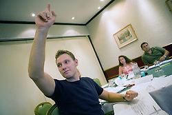 Youth Justice staff member raising his hand to answer a question during training,