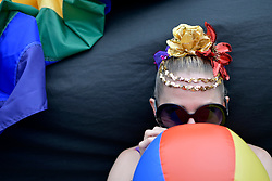 Hoop performer J Hoop, Jennifer Alvarez, of Philadelphia, PA, blows up a beachball as she sits under the judge's table on Independence Mall, during the 30th Philly Pride Parade, on June 10, 2018, in Philadelphia, PA.
