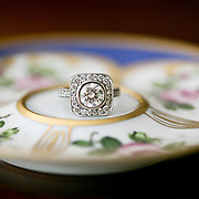 A custom designed ring by Mona Fina rests on a fine china saucer.