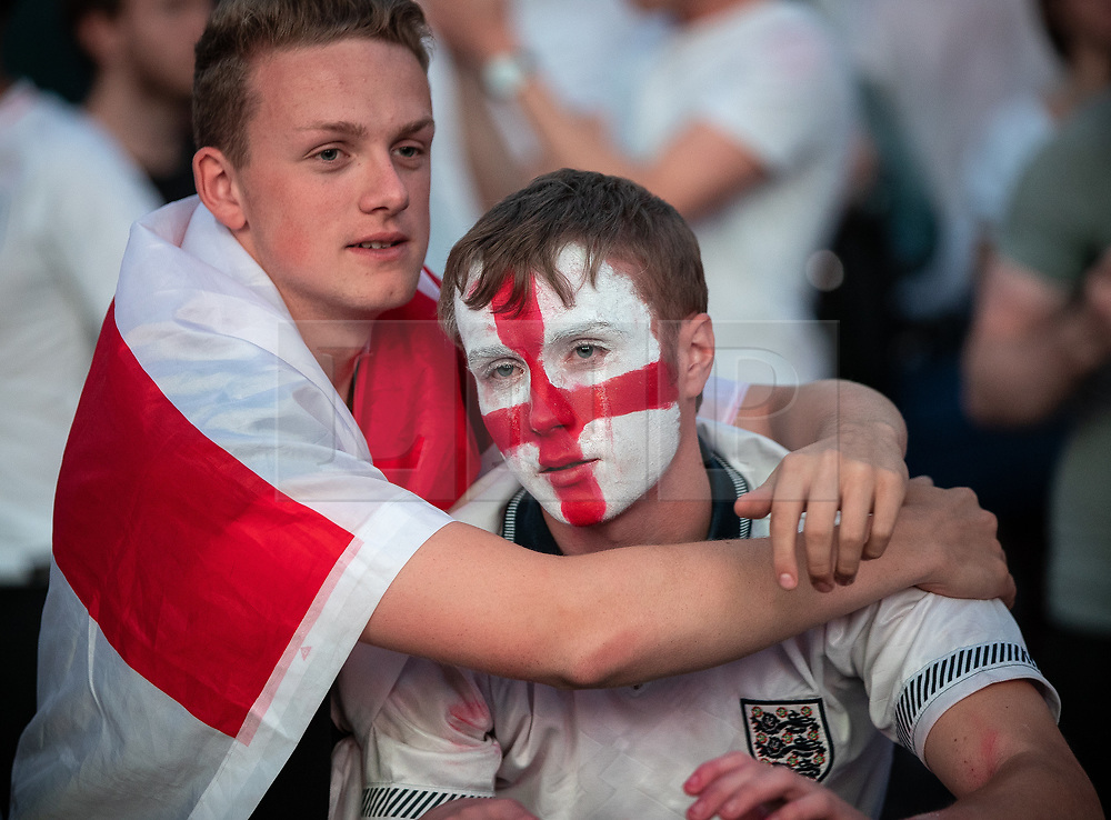 © Licensed to London News Pictures . 11/07/2018. Manchester, UK. An England fan is consoled as he cries as the final whistle blows and England are defeated in the World Cup. England fans watch England play against Croatia in the World Cup semi finals, on a big screen at Castlefield Bowl in Manchester City Centre . Until today , Manchester had been the largest city in England not to be showing World Cup matches to the public on a big screen . Photo credit: Joel Goodman/LNP