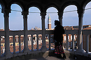 Interior view of woman enjoying the view from the Palazzo Contarini del Bovolo (also called Palazzo Contarini Minelli dal Bovolo). The Palazzo Contarini del Bovolo is a small palace in Venice, best known for the external spiral staircase with a plethora of arches, known as the Scala Contarini del Bovolo (of the snail). The palace dates from the 15th century and is apparently in poor state of restoration, while the staircase leads to an arcade provides a charming panoramic vista over some of the roof-tops of the city. The palace is located in a less-traveled side-street near the Campo Manin, near the Rialto...Subject photograph(s) are copyright Edward McCain. All rights are reserved except those specifically granted by Edward McCain in writing prior to publication...McCain Photography.211 S 4th Avenue.Tucson, AZ 85701-2103.(520) 623-1998.mobile: (520) 990-0999.fax: (520) 623-1190.http://www.mccainphoto.com.edward@mccainphoto.com.