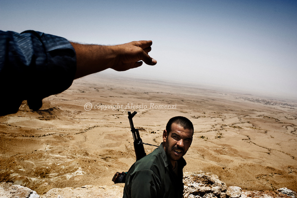 LIBYAN ARAB JAMAHIRIYA, Nalut : A rebel fighter walks near the front line, close to the southwest Libyan village of Gazaia (Top R), as rebels attack forces loyal to Moamer Kadhafi, on July 28, 2011. ALESSIO ROMENZI
