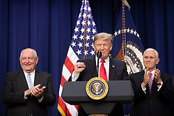 US President Donald Trump delivers remarks, flanked by US Vice President Mike Pence, right, and Secretary of Agriculture Sonny Perdue, left, before signing the Farm Bill into law at the White House in Washington, DC on December 20, 2018. Credit: Alex Edelman / CNP