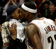 PHOTO BY DAVID RICHARD.LeBron James of the Cavaliers kisses his son LeBron James Jr. after Cleveland erased a large deficit in the second half to defeat Los Angeles March 19 at Quicken Loans Arena.