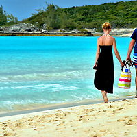 Couple Walking Along Beach at Half Moon Cay, Bahamas<br /> This couple enjoyed strolling along the crescent-shaped beach at Half Moon Cay while the surf gently lapped against their bare feet. They did not have a care in the world, except for carrying their flips flops and a beach bag. If only every day were this wonderful and carefree.