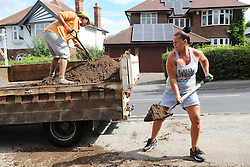 Women shovelling soil into lorry