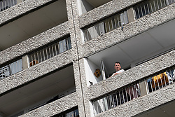 Leith, Edinburgh, Scotland, UK. 7 April 2020. In the third week of the nationwide coronavirus lockdown life in Leith continues although the streets are mostly deserted and shops closed. Pictured; Man on balcony in his flat in  apartment block in Leith.
