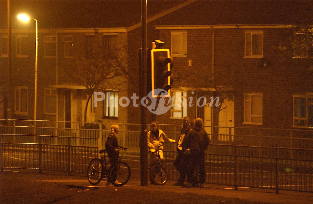 Group of teenage girls hanging about on council housing estate in the evening; Tyneside UK