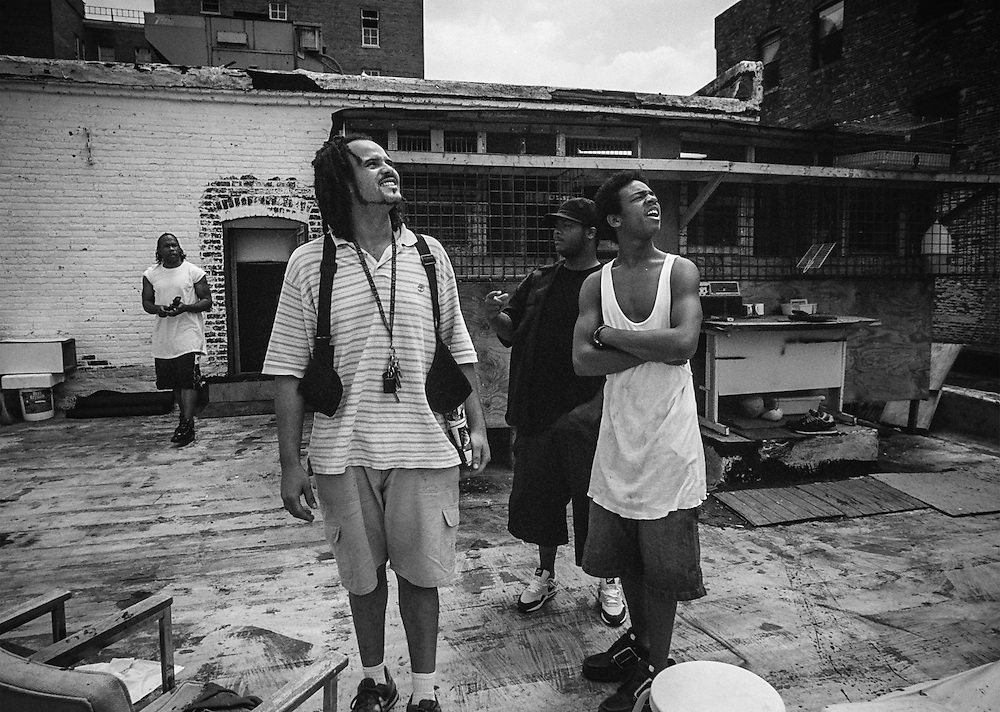 BALTIMORE -- Pigeon racing in Baltimore. Vega Holland (left, foreground), Jerome Henderson (white tank top), and Dashawn Jones watch pigeons fly from the rooftop of New Breed Pigeon Supply.  The man in the background at left is unidentified.… by André F. Chung