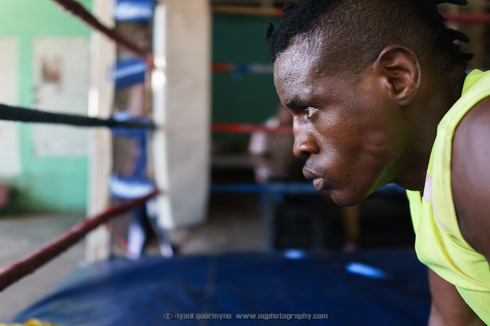 Yomi Shokunbi, a Nigerian living in South Africa, looks out at the street while doing push-ups at the Hillbrow Boxing Club. Currently a model and fitness trainer, he hopes to qualify for his boxing license and become a professional heavyweight boxer.