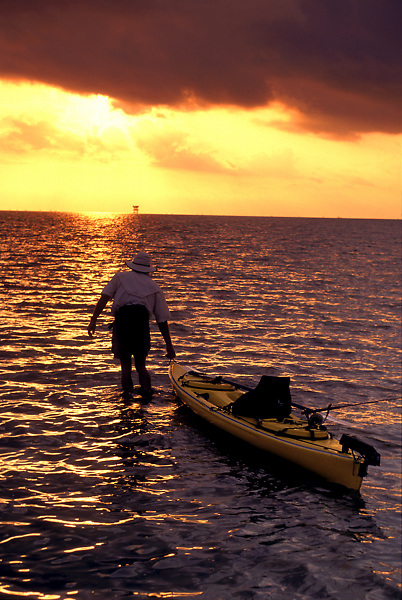 Stock photo of a man walking his kayak out onto the water at sunset