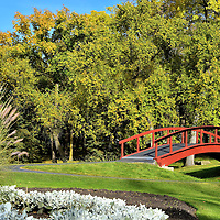 Foot Bridge at Kildonan Park in Winnipeg, Canada<br /> Kildonan Park in the northern part of Winnipeg was created in 1909 to provide 96 acres of green space for the local community.  In features picnic areas and shelters, an outdoor theater, a pavilion, a swimming pool, sports fields, toboggan slides and a skating rink in the winter, a walking path along the Red River and plenty of gardens. This red footbridge is located in the South Garden.