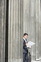 Businessman standing outside building between pillars reading newspaper