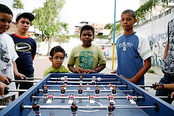 Boys play foosball on a table provided by Alexis Vive in the 23 de Enero barrio.