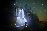 Ethan Welty stands facing Tsusiat Falls at night, spilling onto the beach along the West Coast Trail, British Columbia, Canada.