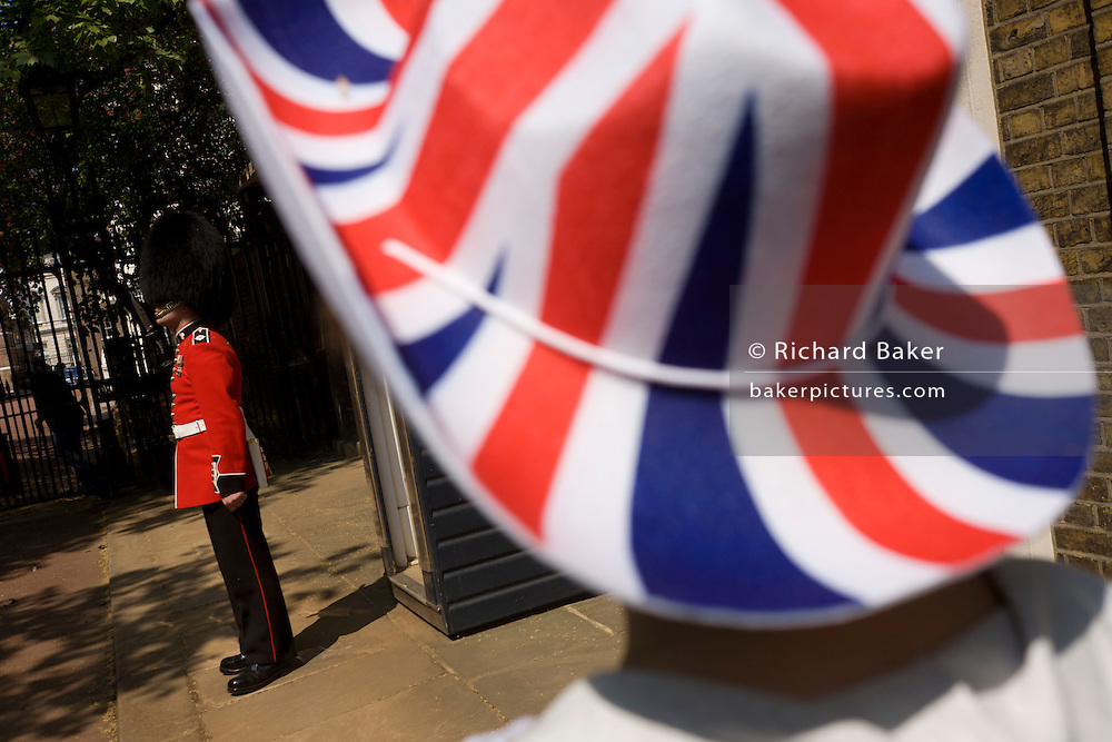 24 hours before the royal marriage of Prince William and Kate Middleton, a guardsman stands by his sentry box in front of Clarence House in St James Palace where the royal bride is staying. A lady royalist stands admiring the soldier in a bright Union Jack-coloured hat as the guardsman stands at attentionin tandem with an unseen colleague. Taking place on Friday 30th April in front of millions of Britons and foreign tourists (many American), the crowds are already gathering to claim their ideal locations in the front rows along the procession route.