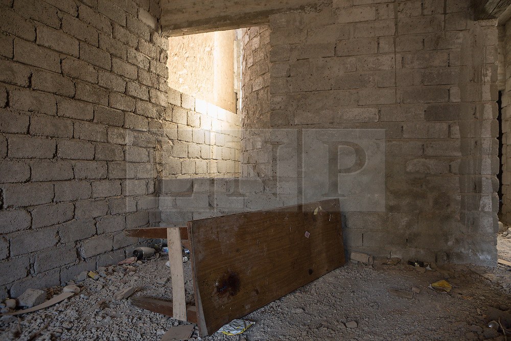 © Licensed to London News Pictures. 04/11/2016. Hamdaniyah, Iraq. A blood stained table, and blood splashed walls are seen in a room thought to have been used by ISIS militants in the recently liberated Iraqi town of Hamdaniyah.<br /> <br /> Although located close to a front line, littered with improvised explosive devices and pieces of unexploded ordnance the Christian town of Hamdaniyah has only recently been cleared of ISIS extremists who stayed behind to fight. After the town's liberation as part of the Mosul Offensive residents and priests of the town are now free to take short trips to assess damage, salvage possessions and clear up the mess left by militants during their two year occupation.<br /> <br /> Hamdaniyah, and much of the Nineveh plains, were captured by the Islamic State during a large offensive on the 7th of August 2014 that saw the extremists advance to within 20km of the Iraqi Kurdish capital Erbil. Residents of the town, who included many Christian refugees who escaped there after the fall of Mosul, were then forced to seek sanctuary in the Kurdish areas. In the year and two months of the ISIS occupation churches were burnt, homes were put into use as militant accommodation and bomb factories and some buildings destroyed by coalition airstrikes. Photo credit: Matt Cetti-Roberts/LNP