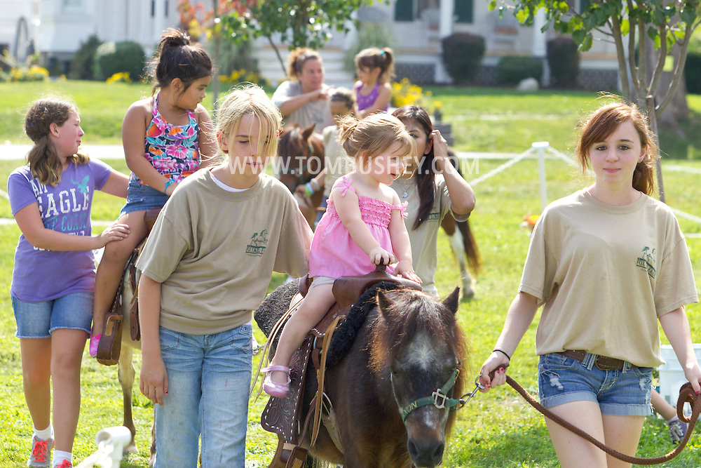 Montgomery, New York - Girls give children rides on ponies during the General Montgomery Day festival on Sept. 8, 2012. ©Tom Bushey / The Image Works