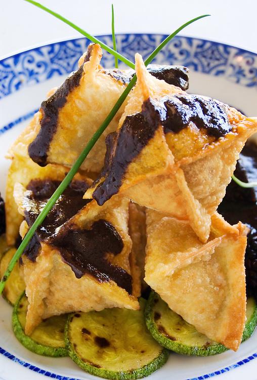 Fried duck ravioli with black mole and zuchini rounds. Ravioles de pato con mole negro y calabacitas.