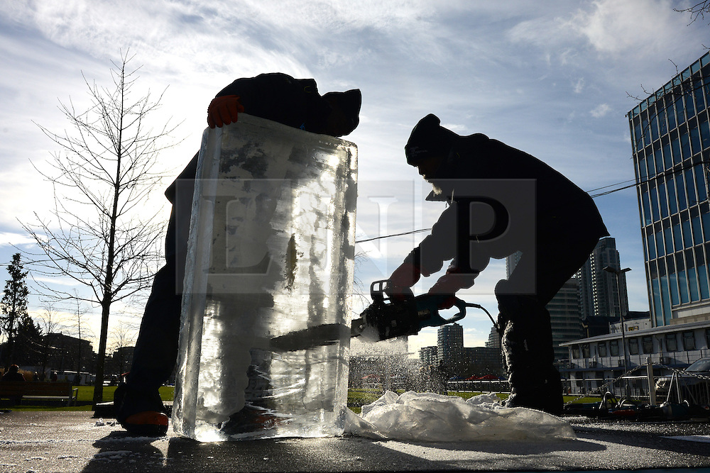 © Licensed to London News Pictures.10/01/2013. London, UK. Members of team Africa create an ice sculpture during the single block ice-sculpting competition at the London Ice Sculpting Festival in Canary Wharf.. Photo credit : Peter Kollanyi/LNP