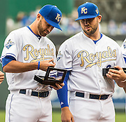 KANSAS CITY, MO - APRIL 5, 2016: Alex Rios #15 of the Kansas City Royals, and his son Alex Rios Jr. stand on the field with Omar Infante #14, Drew Butera #9, Mike Moustakas #8, Lorenzo Cain #6, and Alcides Escobar #2 after receving their 2015 World Series Championship rings during pre-game ceremonies before the game between the New York Mets and the Kansas City Royals at Kauffman Stadium on April 5, 2016 in Kansas City, Missouri. (Photo by Jean Fruth)