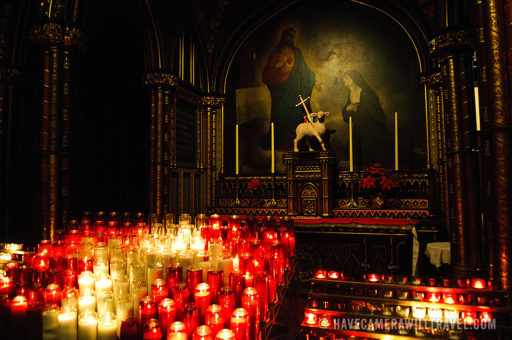 Candles and statues in the ornately decorated Notre-Dame Basilica in Montreal, Canada, a cathedral dating to the middle of the 19th century.