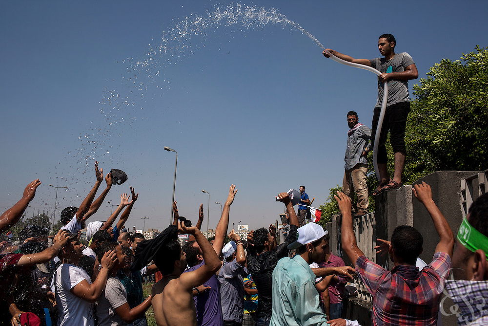 Supporters of deposed Egyptian president Mohamed Morsi try to cool down under a spray of cool water as they march to continuing large scale demonstrations and a sit-in around the Rabaah al-Adawia mosque and square in the Nasr City district of Cairo Friday July 26, 2013.  The supporters are demanding the reinstatement of the deposed President and are opposed to the Egyptian military, which they say has undertaken an undemocratic coup.