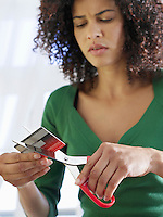 Woman cutting credit card low angle view