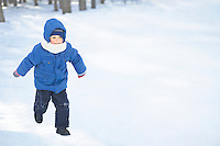 Young boy running in the snow