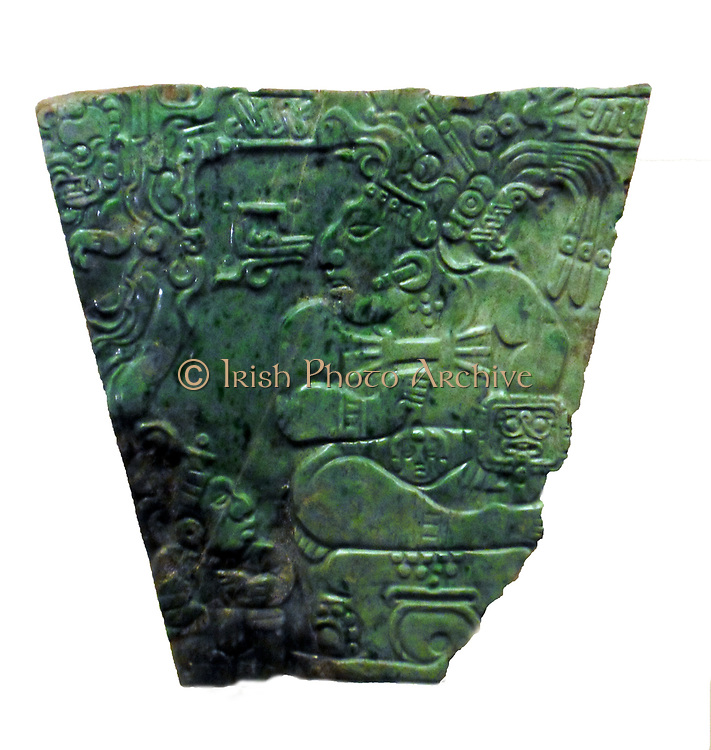 Jade plaque of a Maya king, Mayan Classic period (AD 600-900) Teotihuacan, Mexico. The scene on this plaque, carved in the so-called 'Nebaj style', shows a Maya lord or ruler seated on a throne with a smaller figure at his feet. The lord wears earplugs, a large pectoral, armlets, wristlets, a belt with a mounted head and a zoomorphic headdress decorated with long feathers. On his left arm he carries a shield with a representation of the Jaguar God, a god of the Underworld.