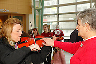 Dayton Philharmonic docent Mary Jane Keeler helps Cathy Bratton of Vandalia try the violin during the 10th Anniversary Open House at the Schuster Center in downtown Dayton, Saturday, March 2, 2013.