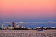 A fishing boat cruises through Biscayne Bay at sunset, past Fisher Island and South Beach condo buildings.<br />