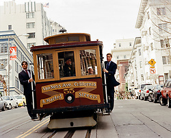 two men in suits riding on the Cable Car in San Francisco, CA