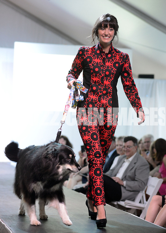 DOYLESTOWN, PA - JUNE 06: A model walks the runway with Lucy the dog during the Canines on the Catwalk fashion show June 6, 2014 at the Michener Museum in Doylestown, Pennsylvania. Canines on the Catwalk is a fashion show coupling professional models, high-end clothes and dogs. The program benefits animal rescue  (Photo by William Thomas Cain/Cain Images)
