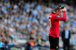 Manchester United's Wayne Rooney picks up his head band after it falls off - Photo mandatory by-line: Dougie Allward/JMP - Tel: Mobile: 07966 386802 22/09/2013 - SPORT - FOOTBALL - City of Manchester Stadium - Manchester - Manchester City V Manchester United - Barclays Premier League