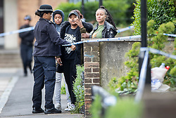 © Licensed to London News Pictures. 02/05/2019. London, UK. A police officer holds back friends and family of the deceased as they view the crime scene at Somerford Grove in Hackney where a 15 year old boy was stabbed to death last night. Scotland Yard say police were called just before 9.00pm.The boy was pronounced dead at the scene at 9.49pm. Photo credit: Peter Macdiarmid/LNP