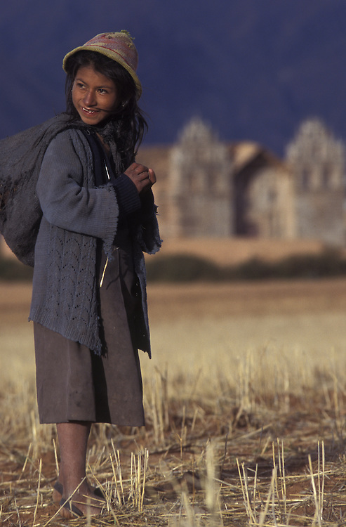 A shepherd girl tends her sheep (out of frame) with the first Spanish church in South America visible in the background.