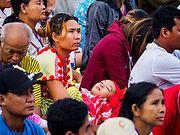 29 NOVEMBER 2017 - YANGON, MYANMAR:  A woman holds her child, dressed in traditional clothes, before the arrival of Pope Francis at the Papal Mass in Yangon. Hundreds of thousands of Catholics from Myanmar attended the mass said by Pope Francis at Kyaikkasan Sports Ground in Yangon Wednesday. Pope Francis is on the first visit by a Pope to Myanmar.PHOTO BY JACK KURTZ