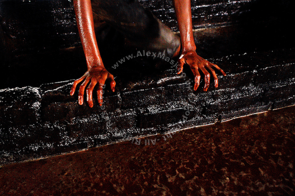 A child labourer in one of the illegal tannery units inside Jajmau, Kanpur, Uttar Pradesh, is holding to the side of a pool while stepping on buffalo's skins inside a bath during the process of liming, the removal of hair and impurities with the use of water and various agents. Children are mostly employed on scraps, or little parts, like the head and the ears of the animal, which will become a small bag or maybe a cheap phone leather case.