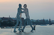 Molecule Man sculpture, designed by American artist Jonathan Borofsky, erected 1999 in the river Spree at An den Treptowers 1, Berlin, Germany. Similar sculptures have been erected in many cities around the world. The sculpture depicts 3 figures meeting and full of holes, representing molecules of all men coming together. In the distance is the Oberbaum bridge. Picture by Manuel Cohen